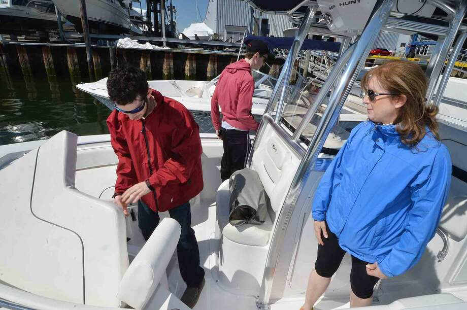The Berger family, Mom Beth with sons Samuel, Jordan and husband Scott get their boat ready at the dock at Rex Marine. Sunday is their first day on the water this season on Sunday morning in Norwalk Conn. on April 17
