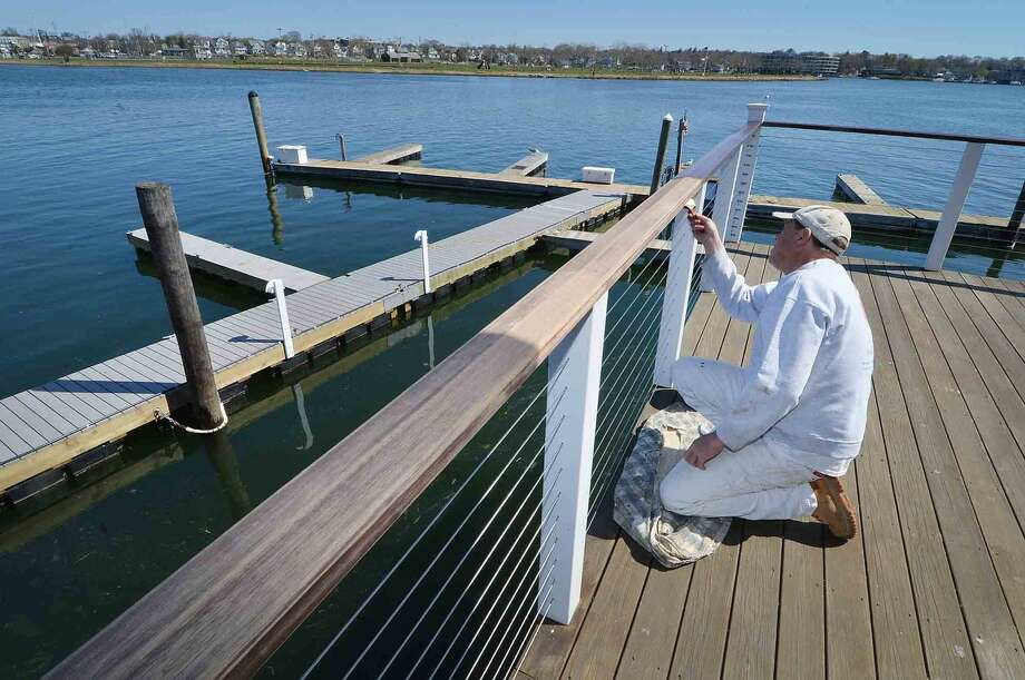 Wayne Embry puts a fresh coat of stain on the deck railings at the Ischoda Yacht Club off Water St in Norwalk, the clubs docks are ready for the season