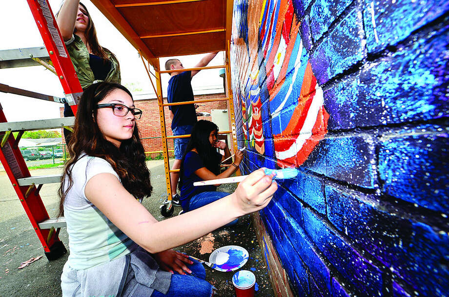 Hour photo / Erik Trautmann West Rocks Middle School 8th graders including Yuliana Soborio paint an outside mural as their parting gift to school continuing a long tradition of mural painting by 8th grade art classes.