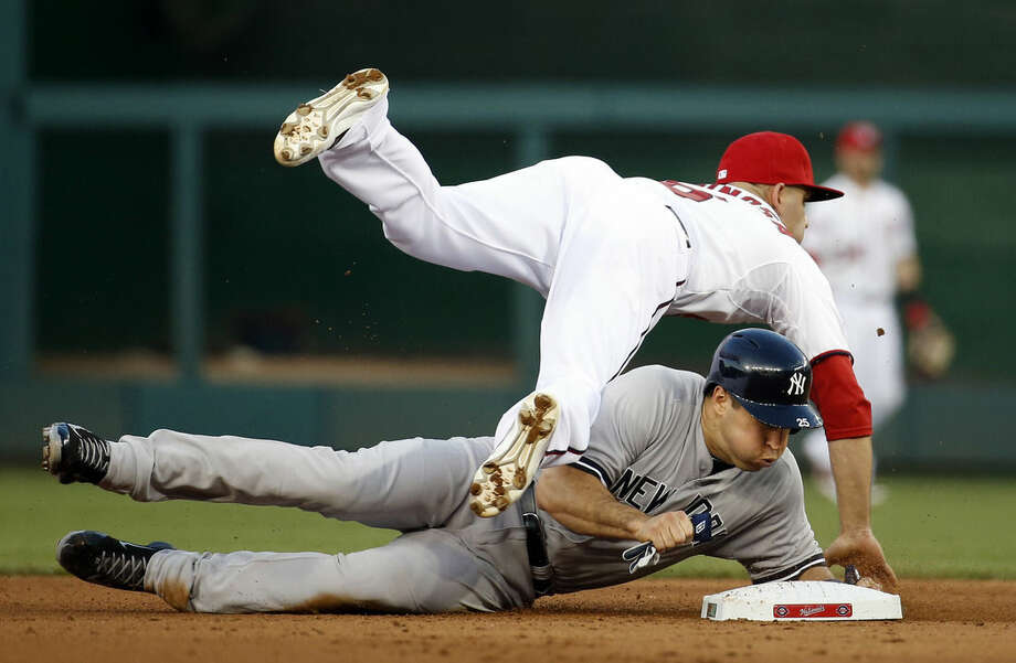 Washington Nationals second baseman Danny Espinosa (8) falls over New York Yankees' Mark Teixeira (25) who is out at second, but breaks up the double play attempt ,during the fourth inning of an interleague baseball game at Nationals Park, Tuesday, May 19, 2015, in Washington. (AP Photo/Alex Brandon)