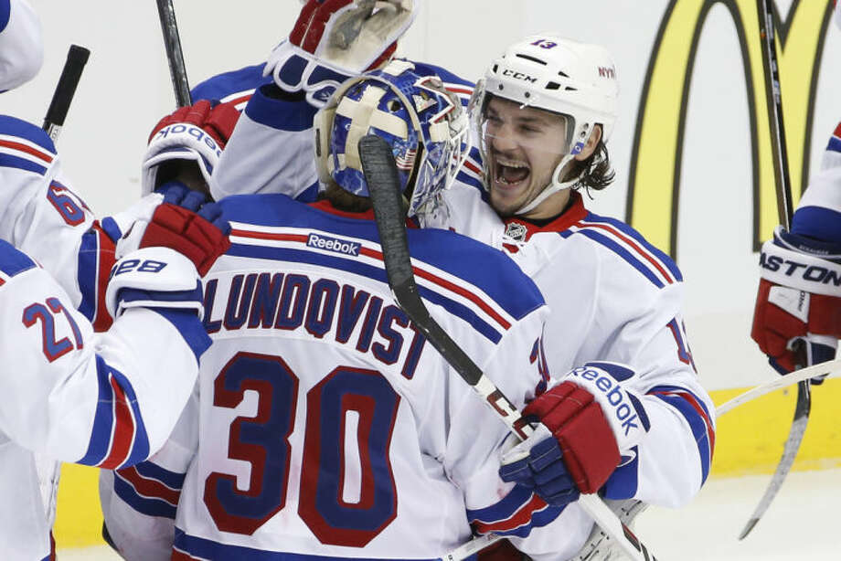 New York Rangers goalie Henrik Lundqvist (30) celebrates with teammate Daniel Carcillo (13) after a 3-2 overtime win in Game 1 of a second-round NHL hockey playoff series against the Pittsburgh Penguins in Pittsburgh, Friday, May 2, 2014. (AP Photo/Gene J. Puskar)