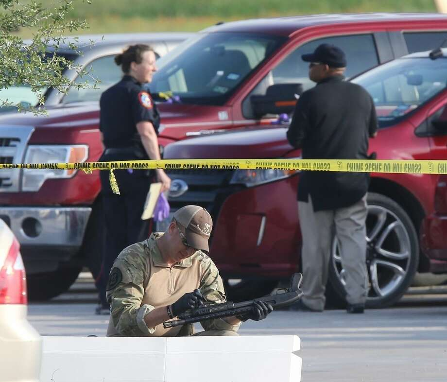A police officer recovers a rifle while sweeping through the parking lot of a Twin Peaks restaurant Tuesday, May, 19, 2015, in Waco, Texas. A deadly weekend shootout involving rival motorcycle gangs at the restaurant apparently began with a parking dispute and someone running over a gang member's foot, police said Tuesday. (Jerry Larson/Waco Tribune-Herald via AP)