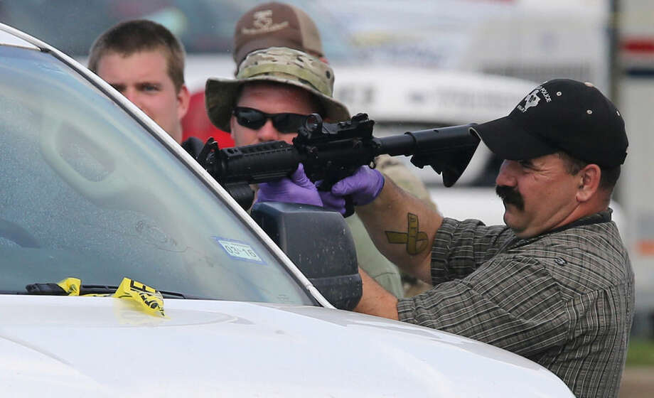 A law enforcement officer uses a rifle to break the window of a vehicle in the parking lot of a Twin Peaks restaurant Tuesday, May, 19, 2015, in Waco, Texas. A deadly weekend shootout involving rival motorcycle gangs at the restaurant apparently began with a parking dispute and someone running over a gang member's foot, police said Tuesday. (Jerry Larson/Waco Tribune-Herald via AP)
