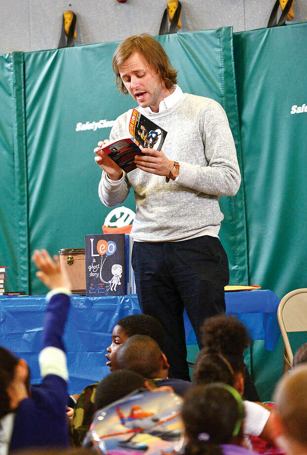 Hour photo / Erik Trautmann Mac Barnett, 2 time Caldacott winner and New York Times best selling author reads from one of his Brixton Brothers mystery novels for students at Fox Run Elementary School Wednesday.