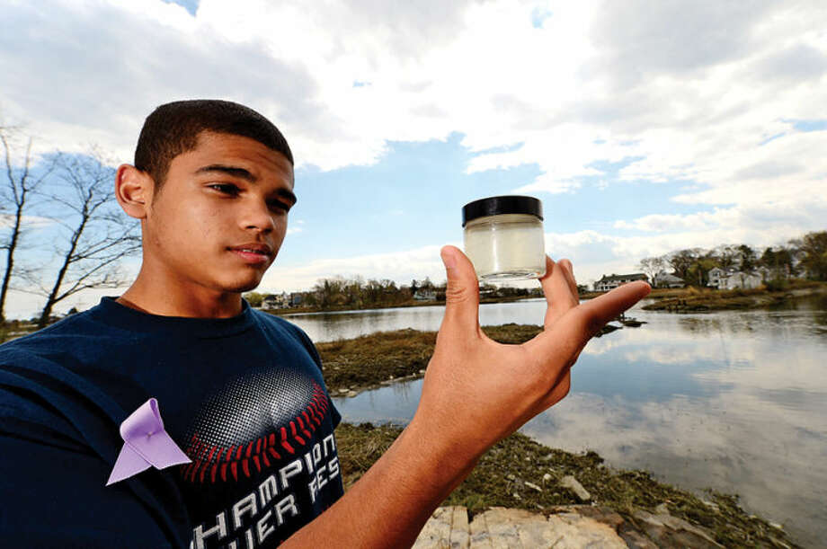 Hour photo / Erik Trautmann Junior Jose Marquez examines a brackish water sample as 80 Norwalk High School chemistry students tour the Shoendorf, Farm Creek preserve estuary performing enviromental testing Friday morning.