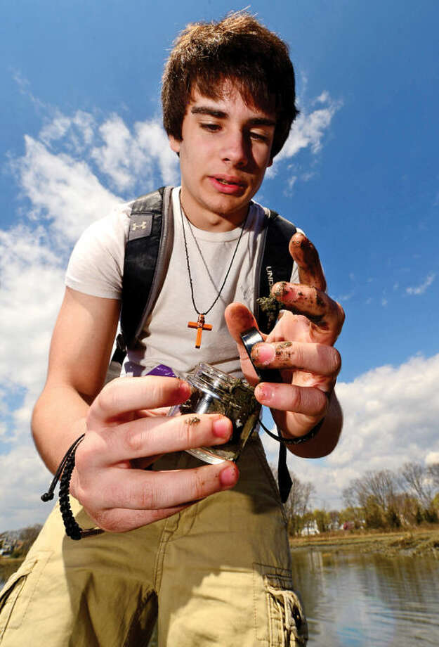 Hour photo / Erik Trautmann Junior Mike Falbo takes a mud sample as 80 Norwalk High School chemistry students tour the Shoendorf, Farm Creek preserve estuary perfroming enviromental testing Friday morning.