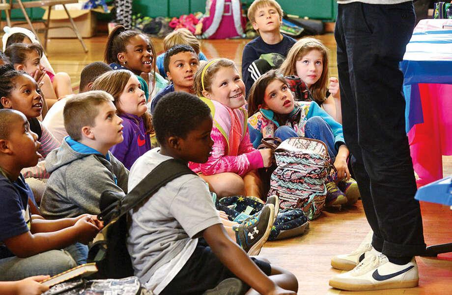 Hour photo / Erik Trautmann Students at Fox Run Elementary School listen to Mac Barnett, a 2 time Caldacott winner and New York Times best selling author read at the school Wednesday.