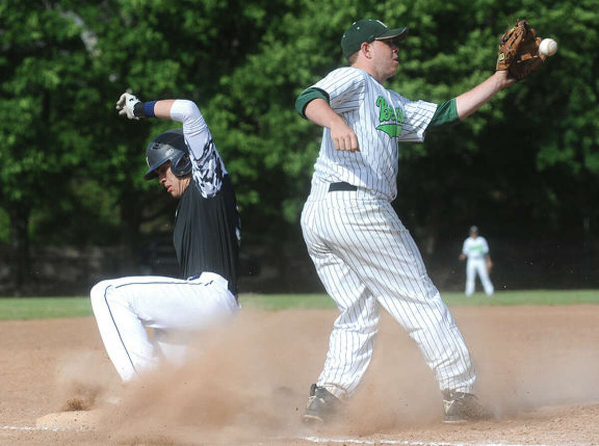 Staples Ross Poulley safe at third and will go to score the first run against Norwalk. # 8 Norwalk Eddie O'Hara. Hour photo/Matthew Vinci