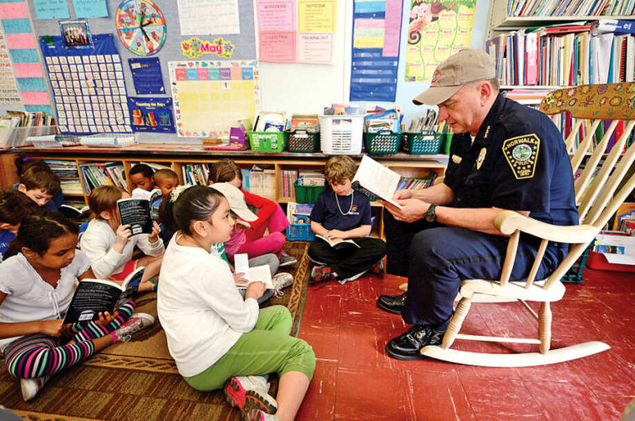 "Hour photo / Erik Trautmann Norwalk Police Chief Thomas Kulhawik reads ""Winners Take All"" by Fred Bowen Friday as part of the ""One Book, One School"" intiative where Cranbury Elementary School spent the last few weeks reading the same book."
