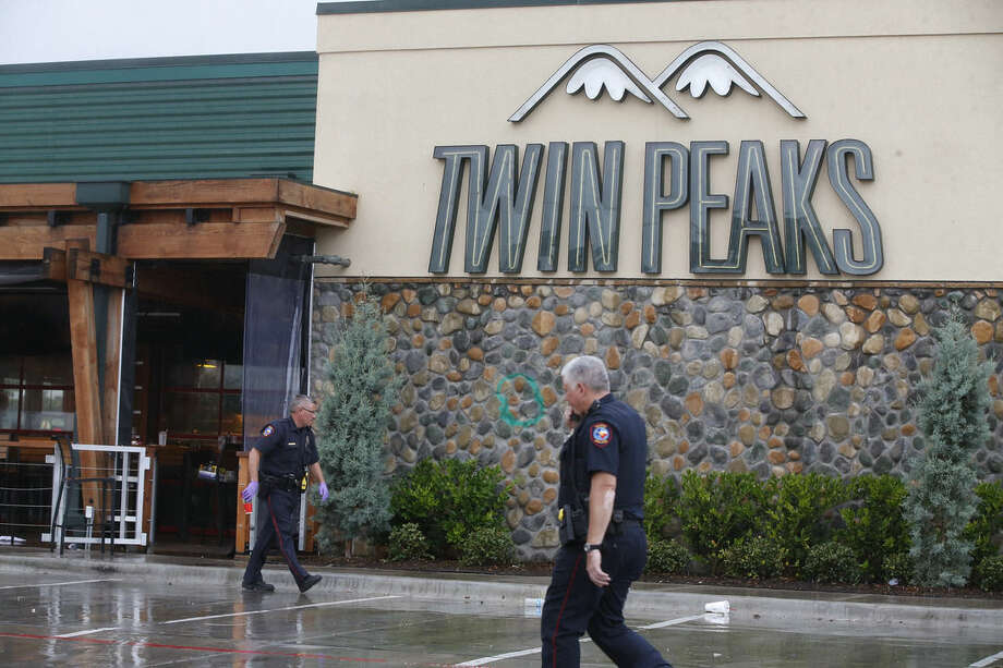 Waco police officers walk along the perimeter of Twin Peaks restaurant during an investigation Wednesday, May 20, 2015 in Waco, Texas. A deadly weekend shootout involving rival motorcycle gangs apparently began with a parking dispute and someone running over a gang member's foot, police said Tuesday. (Rod Aydelotte/Waco Tribune Herald, via AP)