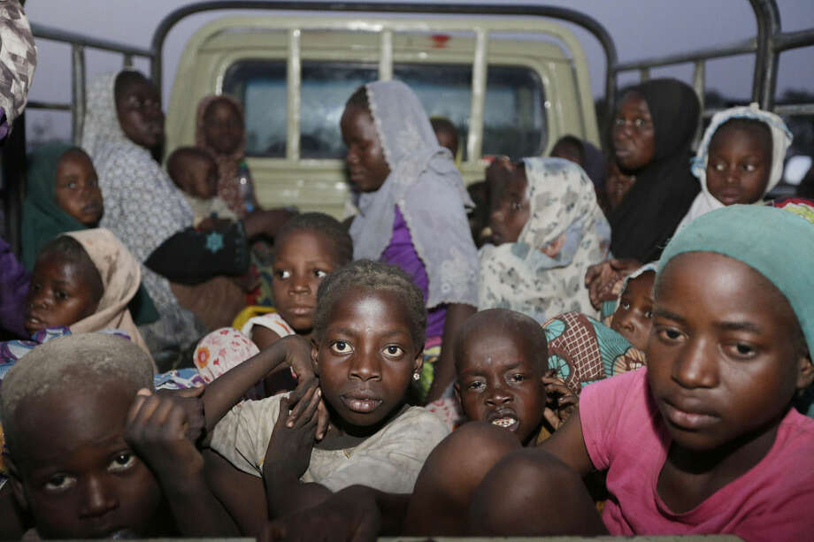 FILE - In this Saturday May 2, 2015 file photo, women and children rescued by Nigeria soldiers from Islamist extremists at Sambisa forest arrive at a camp for the displaced people in Yola, Nigeria. All 275 women, girls and children rescued from Boko Haram and taken to the safety of a northeast Nigerian refugee camp have been taken into military custody amid suspicions that some are aiding the Islamic extremists, a camp official and a Nigerian military intelligence officer said Wednesday May 20, 2015. (AP Photo/Sunday Alamba File)