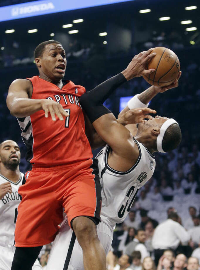 Toronto Raptors' Kyle Lowry (7) fights for control of the ball with Brooklyn Nets' Paul Pierce (34) during the first half of Game 6 of the opening-round NBA basketball playoff series Friday, May 2, 2014, in New York. (AP Photo/Frank Franklin II)