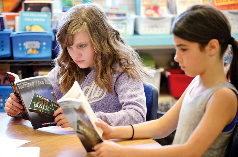 "Hour photo / Erik Trautmann Cranbury Elementary School 4th grade students Lily Guilbault and Charli D'Amelio read ""Winners Take All"" by Fred Bowen with guest reader Mayor Harry Rilling Friday as part of the ""One Book, One School"" intiative where the school spent the last few weeks reading the same book."