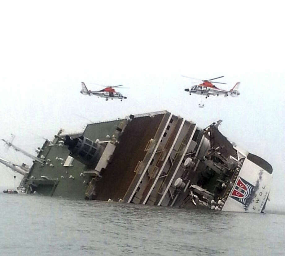 In this Wednesday, April 16, 2014 file photo, South Korean rescue helicopters fly over a South Korean passenger ship, trying to rescue passengers from the ship in water off the southern coast in South Korea. The doomed ferry Sewol exceeded its cargo limit on 246 trips - nearly every voyage it made in which it reported cargo - in the 13 months before it sank, according to documents that reveal the regulatory failures that allowed passengers by the hundreds to set off on an unsafe vessel. And it may have been more overloaded than ever on its final journey. (AP Photo/Yonhap, File) KOREA OUT