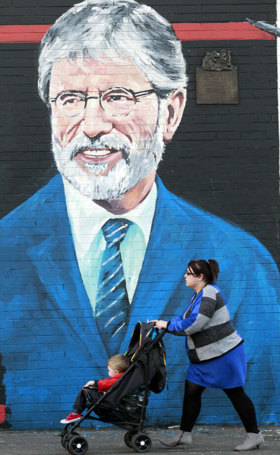 A woman and child make their way past a newly painted mural of Gerry Adams on the Falls Road, West Belfast, Northern Ireland, Friday, May, 2 2014. Police continue to question the Sinn Fein leader Gerry Adams at Antrim police station about the 1972 murder of Jean McConville. (AP Photo/Peter Morrison)