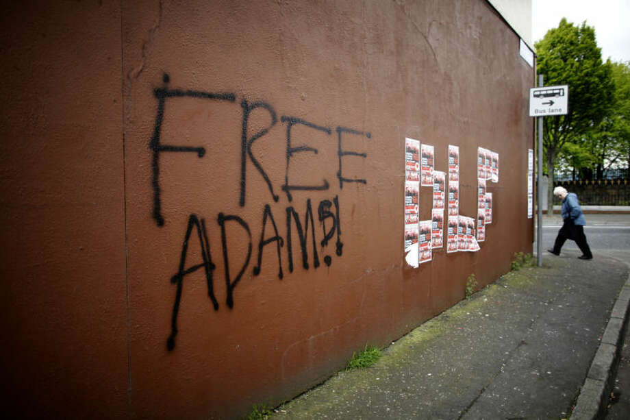 """Free Adams"" is seen written on a wall on the Falls Road, West Belfast, Northern Ireland, Saturday, May, 3, 2014. Police continue to question the Sinn Fein leader Gerry Adams at Antrim police station about the 1972 murder of Jean McConville. (AP Photo/Peter Morrison)"