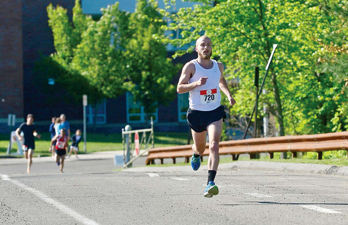 Hour photo / Erik Trautmann James Bloom finishes first in the annual Weston Memorial Day 5k Road Race Saturday.