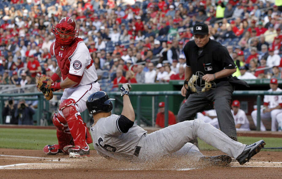 New York Yankees Carlos Beltran (36) slides safely into home with Washington Nationals catcher Wilson Ramos (40) and home plate umpire Marvin Hudson watching, during the first inning of a baseball game at Nationals Park, Wednesday, May 20, 2015, in Washington. (AP Photo/Alex Brandon)