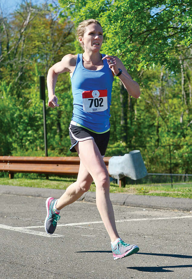 Hour photo / Erik Trautmann Meredith Anand finishes first for the women in the Weston Memorial Day 5k Road Race Saturday.