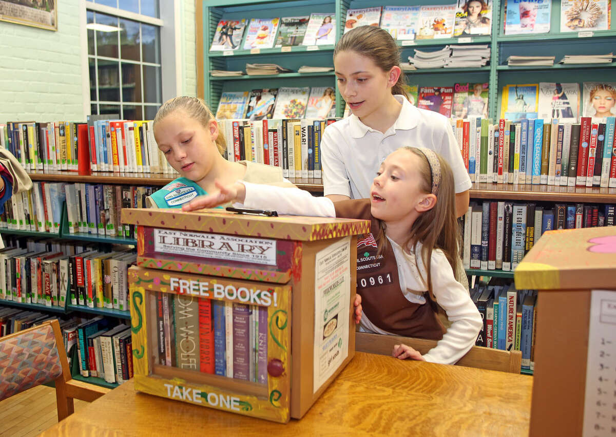 """Girl Scouts Morgan Veltri, 11, Tara O' Connor, 11 and Leigha Fudale, 6 1/2 show off the book nook they made at the East Norwalk Library Friday evening. As part of its """"extension services"""" effort, the East Norwalk Association Library will be placing """"Little Free Library"""" Book Nooks are various locations within the East Norwalk Community. Hour Photo / Danielle Calloway"""
