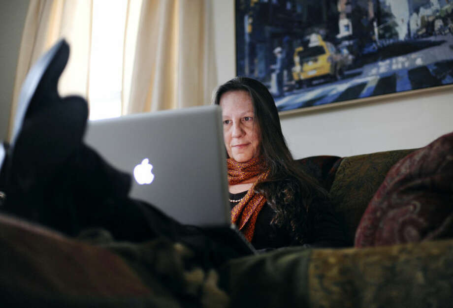 In this Thursday, May 1, 2014 photo, Website designer Dorry Clay, works on her laptop at her home in Stonington, Conn. Clay, who has battled cancer and the effects of the recession, is urging Connecticut lawmakers to enact legislation establishing a state-run pension plan accessible to most workers. Lawmakers in Connecticut and other states are responding to a widespread loss of private-sector pensions, a lack of access to employer-sponsored retirement accounts in smaller businesses and stagnant incomes that make it hard for workers to contribute to their own retirement plan or company account. (AP Photo/Jessica Hill)
