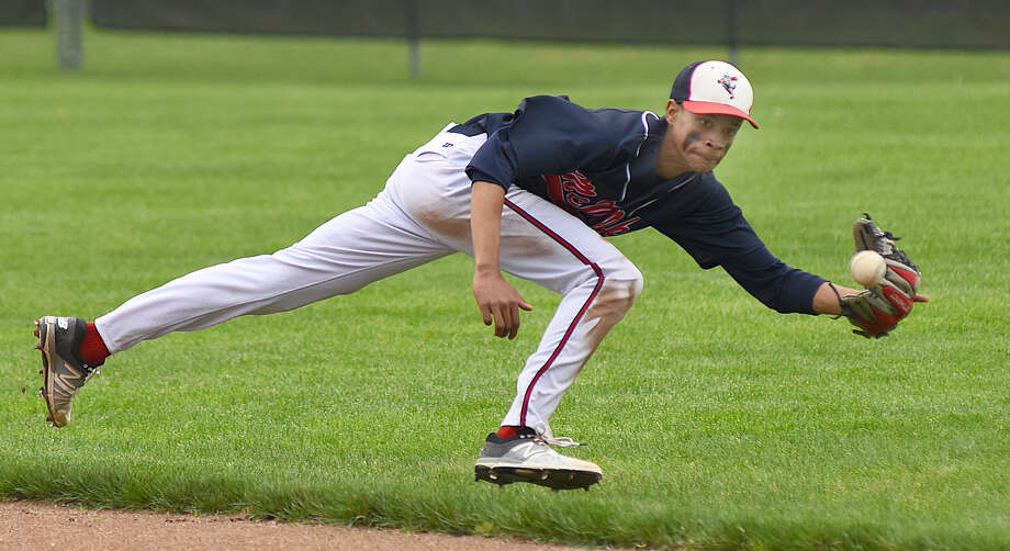 Brien McMahon second baseman Wady Almonte keeps his eyes on the ball as he tracks down a play deep into the hole during Saturday's FCIAC baseball game in Greenwich. The Cardinal won the game, 7-1, to eliminate the Senators from FCIAC playoff contention.
