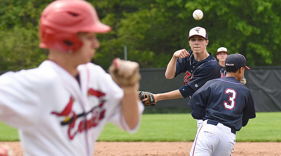 Brien McMahon pitcher Jeff Vitatoe, center, makes an off-balance throw to first base after nearly colliding with second baseman Wady Almonte (3) while throwing out Greenwich batter Ryan King during Saturday's game in Greenwich. The host Cardinals eliminated Brien McMahon from FCIAC playoff contention with a 7-1 win.