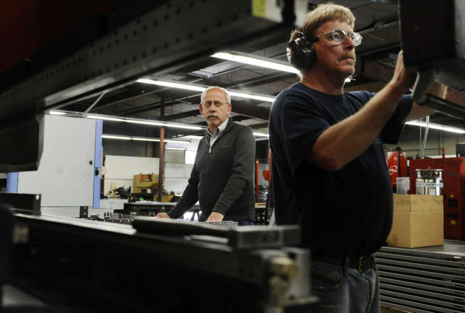 In this Thursday, May 1, 2014 photo, Lou Tashash, owner and president of R-D Manufacturing Inc., left, watches break operator Scott Finlayson work at his precision sheet manufacturing business in East Lyme, Conn. Tashash, who employs 14 workers, is lobbying legislators to kill a measure to establish a state-run pension plan, which he sees as a burdensome mandate. Lawmakers in Connecticut and other states are responding to a widespread loss of private-sector pensions, a lack of access to employer-sponsored retirement accounts in smaller businesses and stagnant incomes that make it hard for workers to contribute to their own retirement plan or company account. (AP Photo/Jessica Hill)