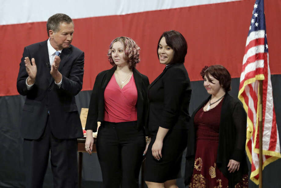 FILE- This Monday, Feb. 24, 2014 file photo shows Ohio Gov. John Kasich, from left, introducing Amanda Berry, Gina DeJesus and Michelle Knight during his State of the State address at the Performing Arts Center in Medina, Ohio. Berry broke through a screen door to freedom last May. Upstairs, officers found DeJesus and Knight. They had been snatched off the streets separately between 2002 and 2004 and locked inside Castro's house where he chained and raped them, investigators later said. (AP Photo/Tony Dejak, File)