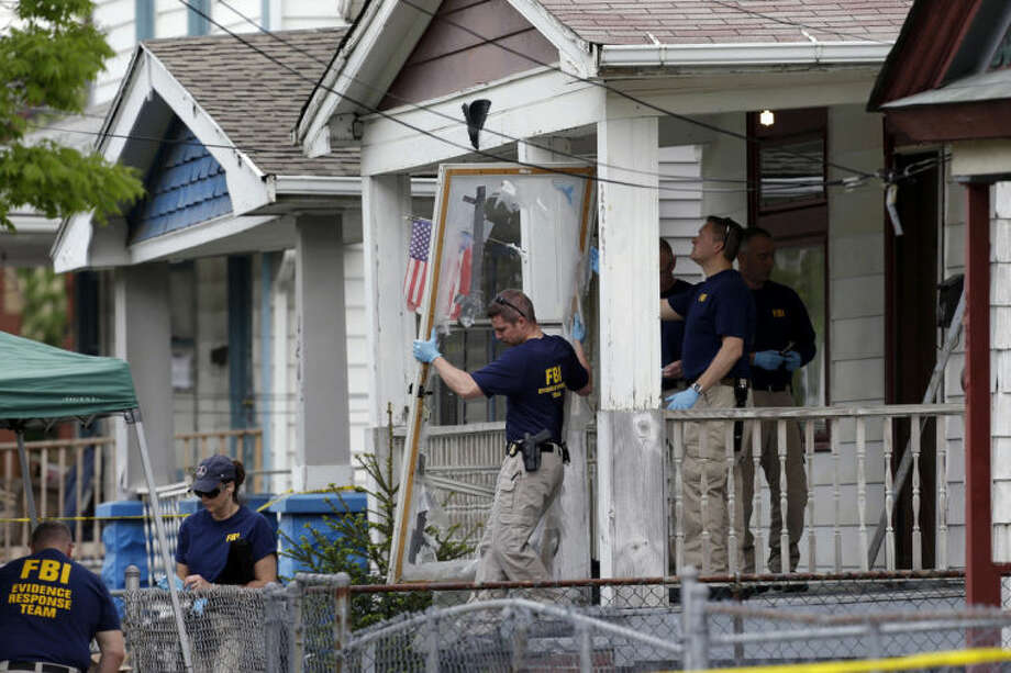 FILE - In this May 7, 2013 file photo, members of the FBI evidence response team carry out the front screen door from the Cleveland home of Ariel Castro, where three women escaped after 10 years of captivity. Amanda Berry broke through the screen door to freedom last May. Upstairs, officers found Gina DeJesus and Michelle Knight. They had been snatched off the streets separately between 2002 and 2004 and locked inside Castro's house where he chained and raped them, investigators later said. (AP Photo/Tony Dejak, File)