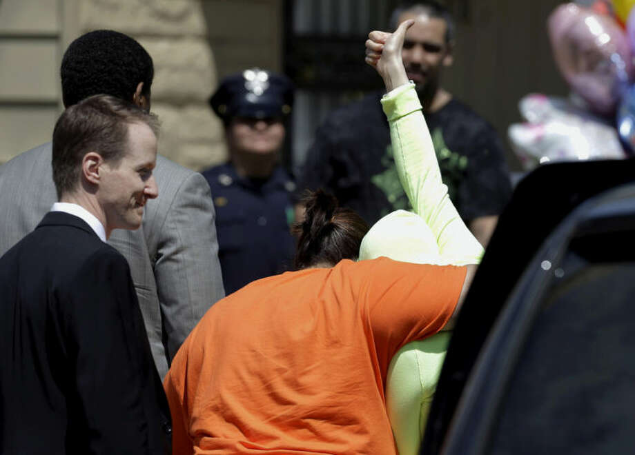 FILE - In this Wednesday, May 8, 2013 file photo, Gina DeJesus gives a thumbs-up as she is escorted toward her home in Cleveland. The list of missing people in Cleveland makes up about one out of every 10 cases in the entire state. Most are found within a few weeks, but there are more than 22 people who have been gone for more than a year. (AP Photo/Tony Dejak, File)