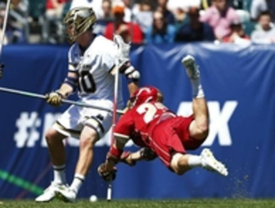 Denver's Mike Riis 23 (23) gets checked after taking a shot and scoring a goal as Notre Dame's Edwin Glazener (30) watches during the third quarter in a semifinal match in the NCAA Division I men's lacrosse tournament, Saturday, May 23, 2015, Philadelphia. (AP Photo/Rich Schultz)
