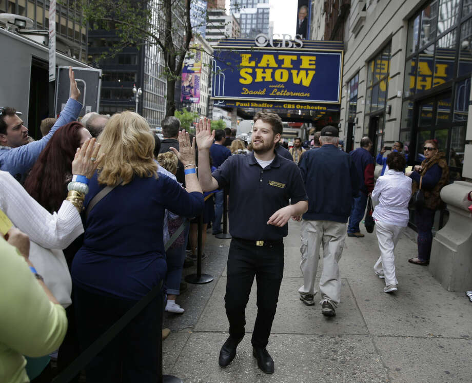 People with tickets to David Letterman's last show wait in line in front of the Ed Sullivan Theater in New York, Wednesday, May 20, 2015. After 33 years and 6,028 broadcasts of his late-night show, David Letterman is retiring. (AP Photo/Seth Wenig)