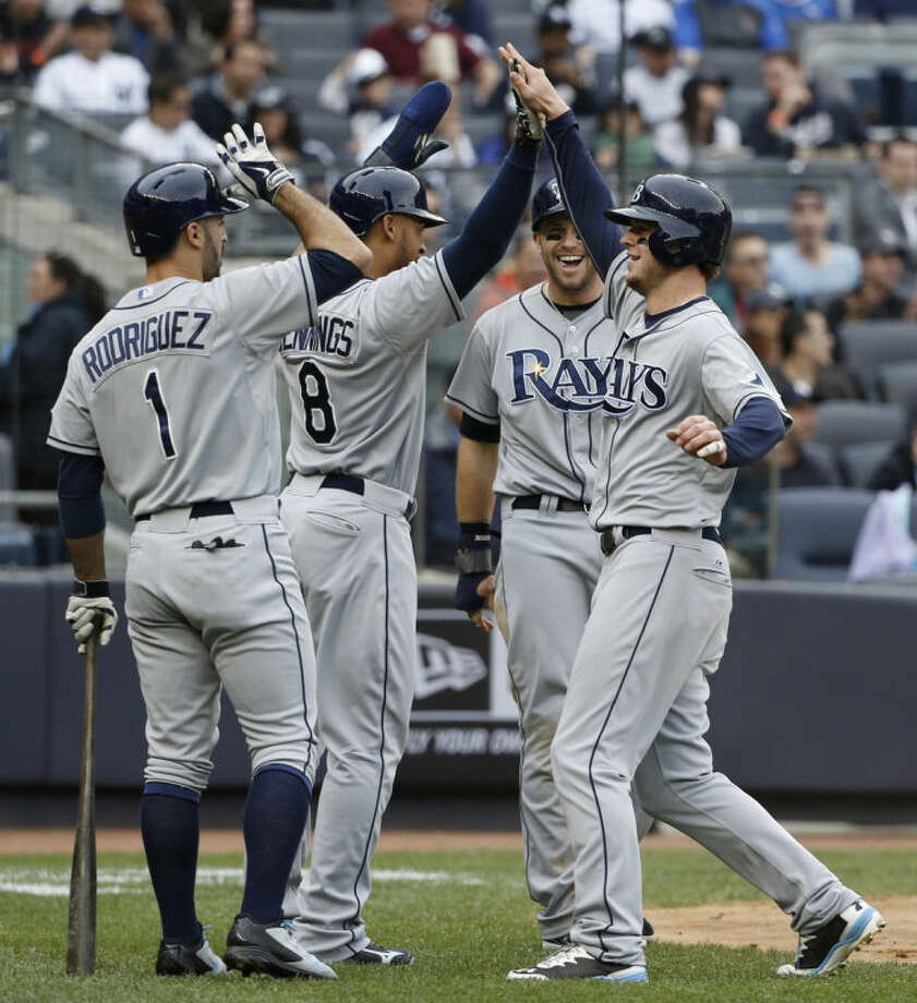 From left to right, Tampa Bay Rays on-deck batter Sean Rodriguez, Desmond Jennings and Evan Longoria greet Wil Myers after Jennings and Longoria scored on Myers' third-inning inside-the-park home run during a baseball game at Yankee Stadium in New York, Sunday, May 4, 2014. (AP Photo/Kathy Willens)