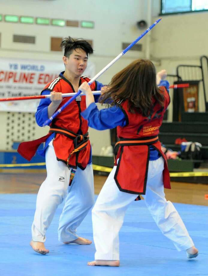 Nicky Bellusci, 17, and his sister Nina Bellusci, 16, both Third Degree Black Belt, perform a matials arts demonstration of stick fighting during the YB World Taekwondo Academy championship tournament at Rippowam Middle School in Stamford on May 14, 2016.