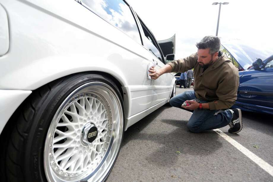 Al DeCarlo, of Stamford, cleans his 1989 BMW 325is during the car show at the J.M. Wright Technical School on Sunday, May 15, 2016.