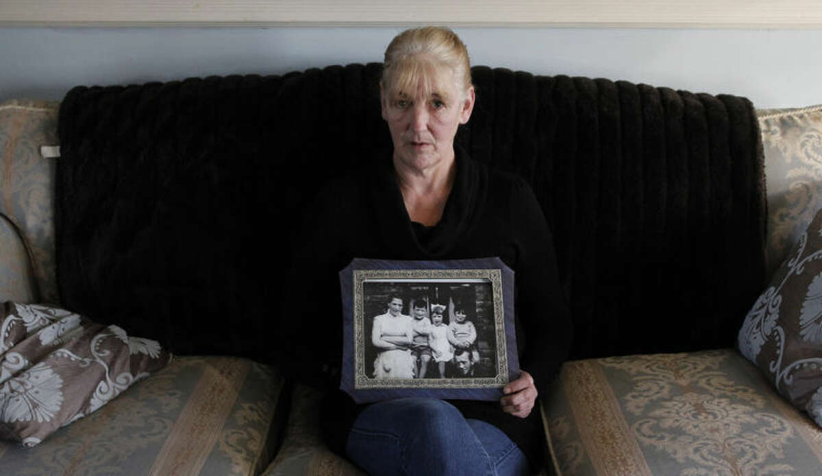 FILE - In this Thursday Jan. 12, 2012 file photo, Helen McKendry holds a family photograph showing her mother Jean McConcille, at home in Killyleagh, Northern Ireland. Police in Northern Ireland arrested Sinn Fein party leader Gerry Adams on Wednesday over his alleged involvement in the Irish Republican Army's 1972 abduction, killing and secret burial of a Belfast widow. Adams, 65, confirmed his own arrest in a prepared statement and described it as a voluntary, prearranged interview. Police long had been expected to question Adams about the killing of Jean McConville, a 38-year-old mother of 10 whom the IRA killed with a single gunshot to the head as an alleged spy. According to all authoritative histories of the Sinn Fein-IRA movement, Adams served as an IRA commander for decades, but he has always denied holding any position in the outlawed group. (AP Photo/Peter Morrison, file)