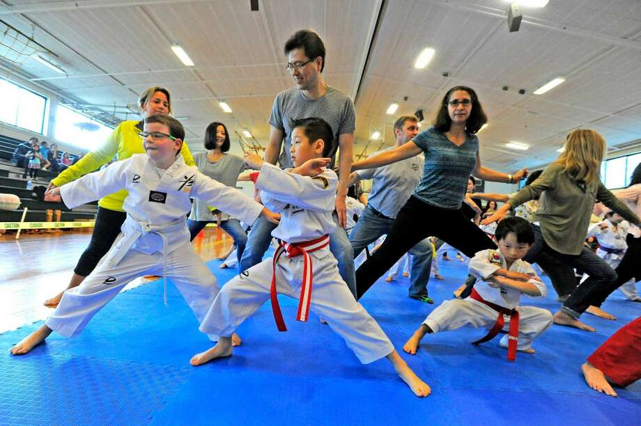From left, James Kolman, 8, Jashan Wu, 5, and Alex Bowbeer, 7, all of Stamford, perform a set of warm up exercises with their parents during the YB World Taekwondo Academy championship tournament at Rippowam Middle School in Stamford on May 14, 2016.