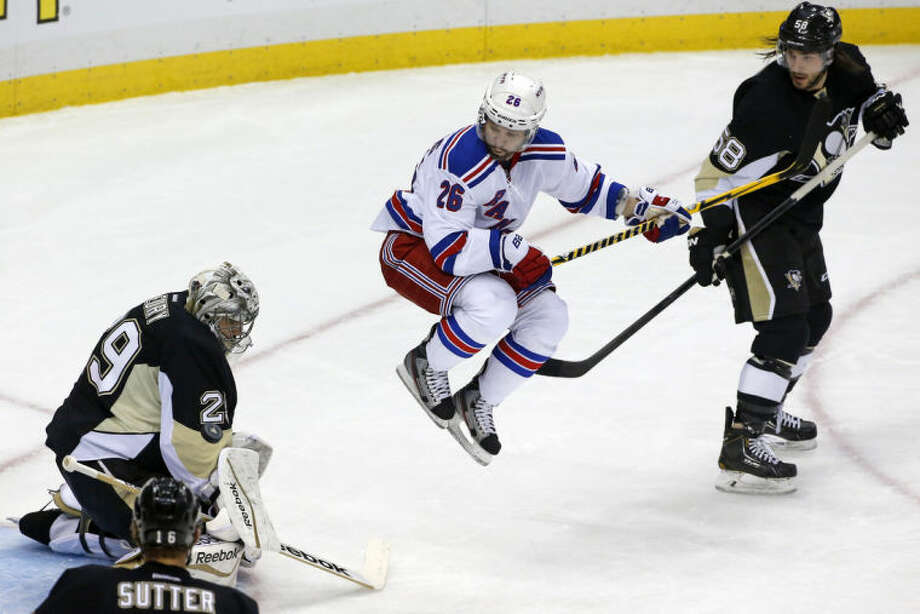 New York Rangers' Martin St. Louis (26) leaps out of the way of a shot between Pittsburgh Penguins goalie Marc-Andre Fleury (29) and Kris Letang (58) in the first period of Game 2 of a second-round NHL playoff hockey series in Pittsburgh, Sunday, May 4, 2014. Penguins' Fleury blocked the shot (AP Photo/Gene J. Puskar)