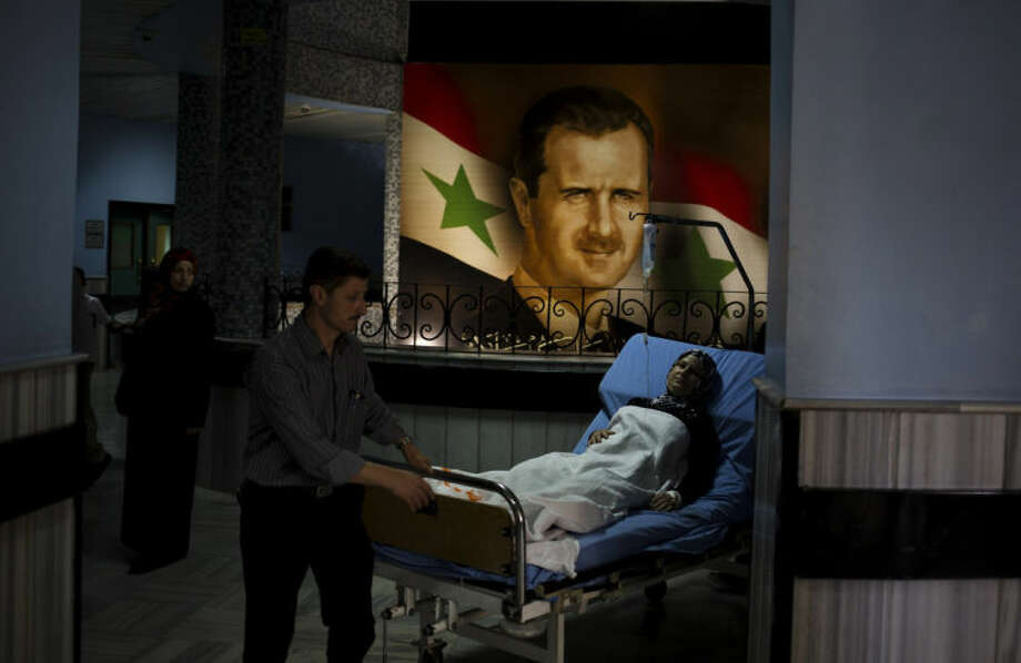 A patient is wheeled through the Damascus General Hospital past a portrait of the President Bashar Assad in Damascus, Syria, Sunday, May 4, 2014. An official with Syria's Supreme constitutional Court said Assad and two others will be candidates in coming June presidential elections. (AP Photo/Dusan Vranic)