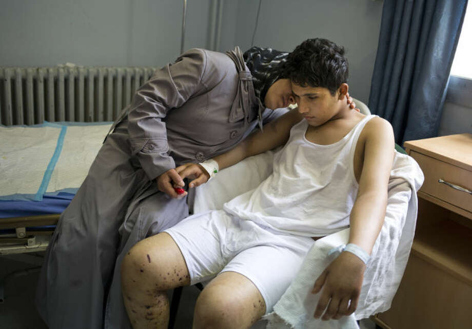Hosen Sabah, a 16-year-old student is comforted by his mother at a hospital in Damascus, Syria, Sunday, May 4, 2014. Nosen was wounded by a mortar outside his school on April 29, 2014, while 14 other students were killed and over 80 wounded. (AP Photo/Dusan Vranic)