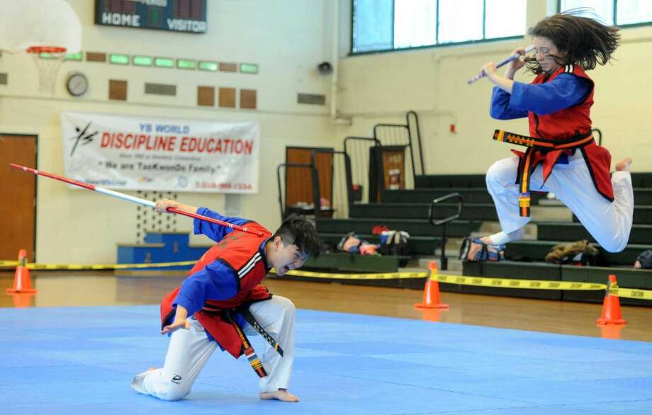 Nicky Bellusci, 17, and his sister, Nina Bellusci, 16, both Third Degree Black Belt, perform a martials arts demonstration of stick fighting during the YB World Taekwondo Academy championship tournament at Rippowam Middle School in Stamford on May 14, 2016.