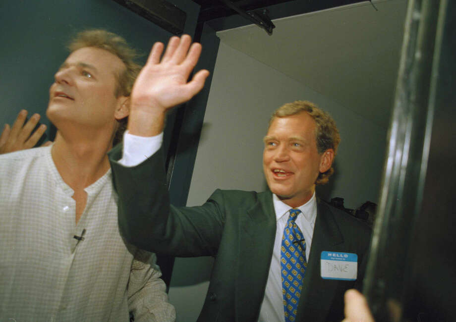 "FILE - In this Aug. 30, 1993 file photo, David Letterman, right, and Bill Murray wave from the side door of the Ed Sullivan Theater during the first episode of ""Late Show with David Letterman"" in New York. After 33 years in late night and 22 years hosting CBS' ""Late Show,"" Letterman will retire on May 20. (AP Photo/Jim Cooper)"