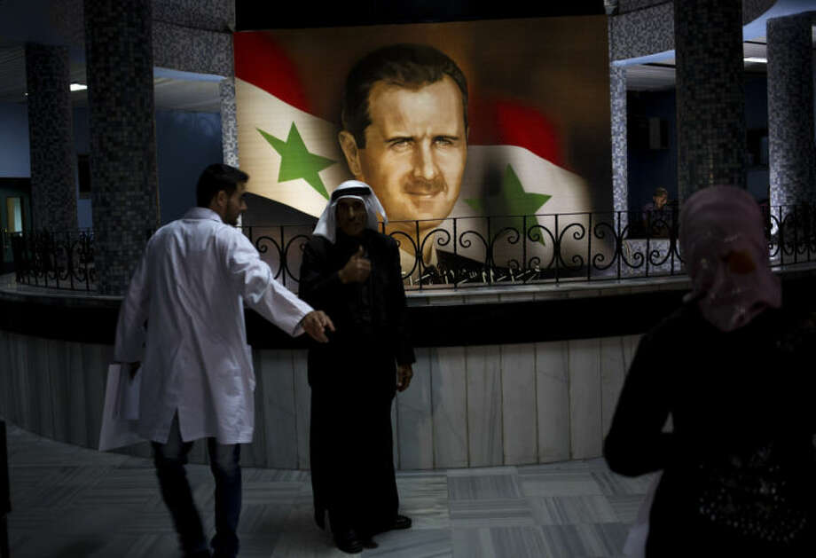 People walk through the Damascus General Hospital past a portrait of the President Bashar Assad in Damascus, Syria, Sunday, May 4, 2014. An official with Syria's Supreme constitutional Court said Assad and two others will be candidates in coming June presidential elections. (AP Photo/Dusan Vranic)