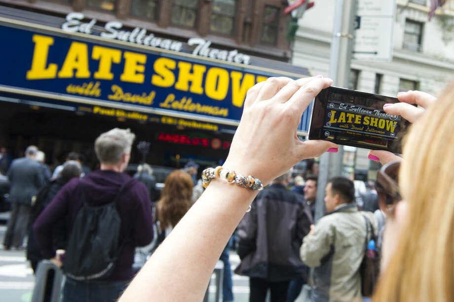 "A fan takes a cell phone photo outside The Ed Sullivan Theater during the last taping of the ""Late Show with David Letterman"" on Wednesday, May 20, 2015, in New York. (Photo by Charles Sykes/Invision/AP)"
