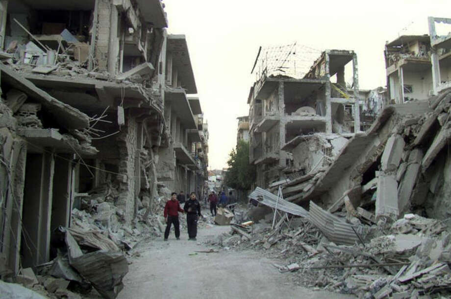 FILE - This file photo released on Thursday Nov. 29, 2012 by the anti-government activist group Homs City Union of The Syrian Revolution, which has been authenticated based on its contents and other AP reporting, shows Syrian citizens walking in a destroyed street that was attacked by Syrian forces warplanes, at Abu al-Hol street in Homs province, Syria. Syria's government and rebels agreed to a ceasefire on Friday, May 2, 2014 in the battleground city of Homs to allow hundreds of fighters holed up in its old quarters to evacuate, a deal that will bring the country's third-largest city under control of forces loyal to President Bashar Assad. (AP Photo/Homs City Union of The Syrian Revolution, File)