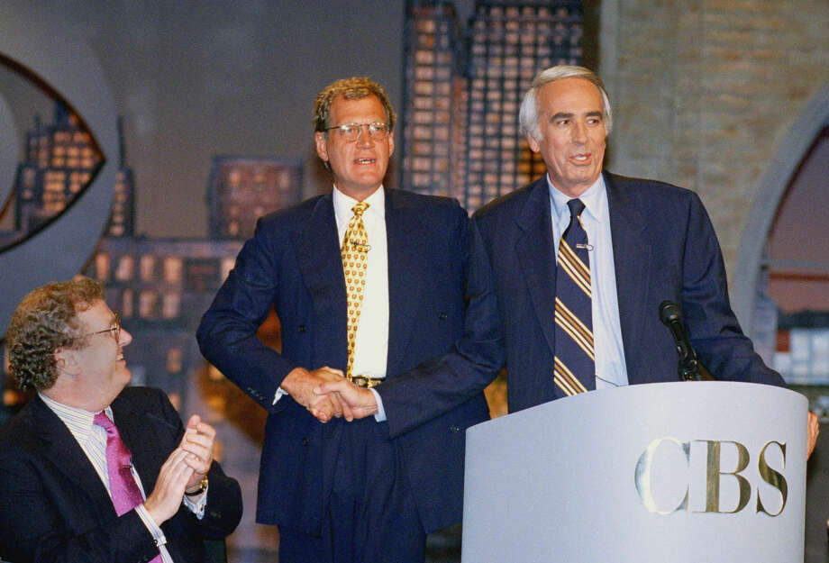 "FILE - In this Aug. 9, 1994 file photo, CBS President Howard Stringer applauds at left as David Letterman, center, shakes hands with Tom Snyder after announcing that Snyder's show with follow Letterman's at New York's Ed Sullivan Theater. Letterman will retire from hosting ""Late Show with David Letterman"" on May 20. (AP Photo/Eric Miller, File)"