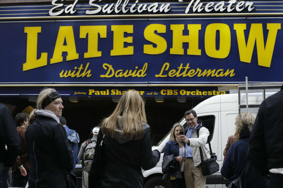 "A couple takes a selfie outside the Ed Sullivan Theater in New York, Wednesday, May 20, 2015. David Letterman signed off Wednesday after 33 years and 6,028 broadcasts of the ""Late Show with David Letterman."" (AP Photo/Mary Altaffer)"