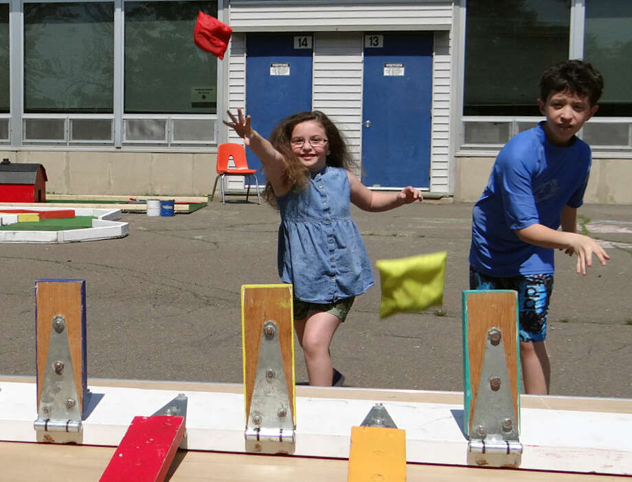 Gabrielle and Michael Prisciadaro, ages 6 and 11, of Fairfield, play the Knock 'Em Down game Saturday at Holland Hill School's fair.