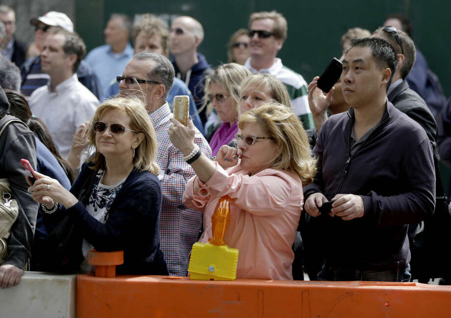 A crowd looks for celebrities across the street from the Ed Sullivan Theater stage door in New York, Wednesday, May 20, 2015. After 33 years and 6,028 broadcasts of his late-night show, David Letterman is retiring. (AP Photo/Seth Wenig)